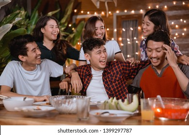 fun young people laughing while having garden party at home and having some dinner