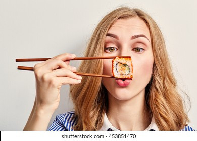 fun young woman eating sushi on white background