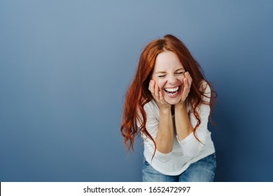 Fun young woman enjoying a good joke laughing loudly with hands to cheeks bending towards the camera on a blue studio background with copy space