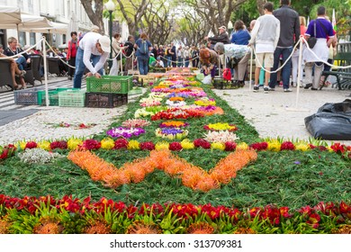 FUNCHAL, MADEIRA - APRIL 16, 2015: In the city centre of Funchal along the central promenade of Avenida Arriaga, the famous floral carpets are created.