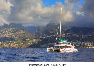 FUNCHAL, MADEIRA - OCTOBER 11, 2015: Tourists sailing around Madeira island on a catamaran looking for dolphins and whales, a popular tourist attraction, on October 11, 2015