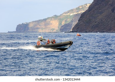 FUNCHAL, MADEIRA - OCTOBER 11, 2015: Coastguard people in a fast zodiac rubber boat speeding in the waters near Funchal, Madeira, on October 11, 2015