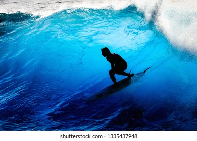 FUNCHAL, MADEIRA - OCTOBER 8, 2015: Silhouette of a unrecognizable surfer riding the big blue surf waves on the island Madeira, Portugal, a popular surfing tourist destination