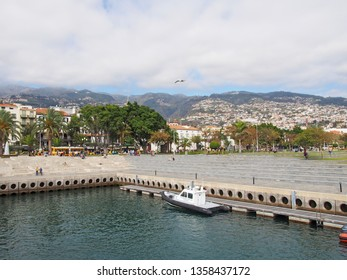 funchal, madeira, portugal - 14 March 2019: the waterfront area of funchal harbour with a coastguard boat moored in the dock people sat on concrete steps with the city and mountains in the background