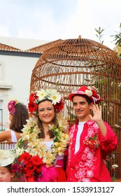 FUNCHAL, MADEIRA, PORTUGAL – APRIL 2018: unidentified woman and man present the local flowers at the flower festival in Funchal on april 22, 2018.