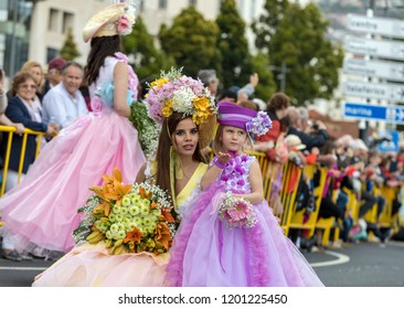 Funchal; Madeira; Portugal - April 22; 2018: Mom and her daughter  in colorful costumes at Madeira Flower Festival Parade in Funchal on the Island of Madeira. Portugal.