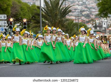 Funchal; Madeira; Portugal - April 22; 2018: A group of girls in colorful dresses with sunflowers motifs are dancing at Madeira Flower Festival Parade in Funchal on the Island of Madeira. Portugal.