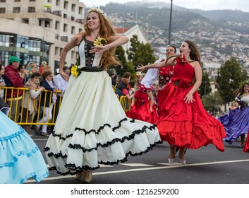 Funchal; Madeira; Portugal - April 22; 2018: A group of people in colorful costumes are dancing at Madeira Flower Festival Parade in Funchal on the Island of Madeira. Portugal.