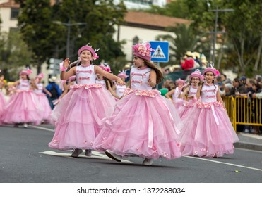 Funchal; Madeira; Portugal - April 22; 2018: A group of girls in pink costumes are dancing at Madeira Flower Festival Parade in Funchal on the Island of Madeira. Portugal.
