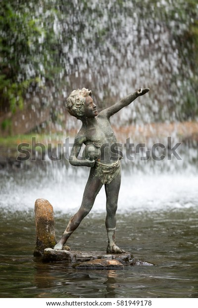 FUNCHAL, MADEIRA, PORTUGAL - SEPTEMBER 2, 2016: Statue of boy in botanical garden Monte of Funchal, Madeira.  Portugal.