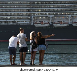 Funchal, Madeira, Portugal - September 2017: A person points out something of interest to her friend with the cruise ship, the QE2, in the background