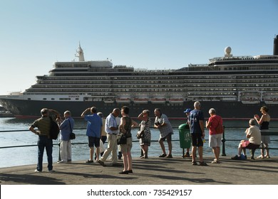 Funchal, Madeira, Portugal - September 2017: A group of tourists look at the cruise liner, the QE2, in the city's harbour
