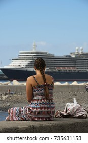 Funchal, Madeira, Portugal - September 2017: A young girl siting on a wall looking out at the cruise liner, the QE2