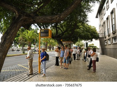 Funchal, Madeira, Portugal - September 2017:  People waiting at a bus stop for a public service bus