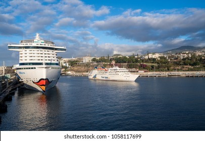FUNCHAL, MADIERA - MARCH 12, 2018: Aidaprima cruise ship docked and Porto Santo ferry leaving harbor at Funchal, Madiera