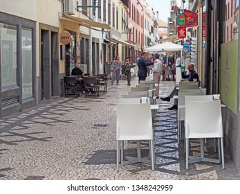 Funchal, Madiera, Portugal - 15 march 2019: People talking in the street and sitting in cafes in a cobbled pedestrian street in the center of Funchal in Madeira