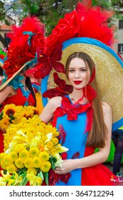 FUNCHAL, PORTUGAL - APRIL 19, 2015: A beautiful woman dressed in floral costume posing in street of Funchal during of Flower Festival (Festa da Flor) The Flower Festival of Madeira is an annual event.