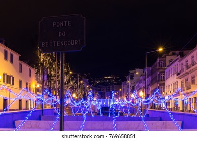 """FUNCHAL, PORTUGAL - DECEMBER 5, 2017: View of Christmas lights on """"Bettencourt"""" bridge through a riverside of Funchal city, Madeira island, Portugal."""