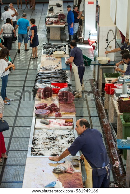 FUNCHAL, PORTUGAL - SEPTEMBER 2, 2016: Fish sellers at Mercado dos Lavradores, the famous fish and seafood market of Funchal, the capital of Madeira island