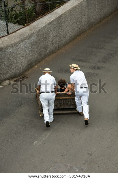 FUNCHAL, PORTUGAL - SEPTEMBER 2, 2016: Toboggan riders moving traditional cane sledge downhill on the streets of Funchal.