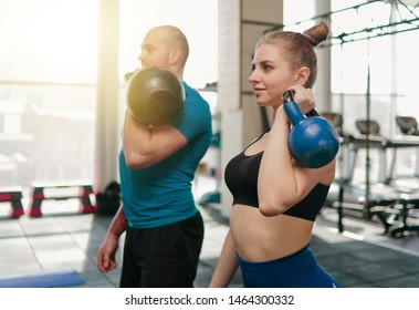 Сouple functional training. Sporty man and fit woman doing exercise with kettlebell in gym