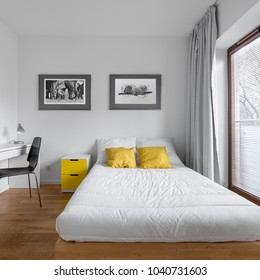 Functional, white bedroom with bed and modern, countertop desk