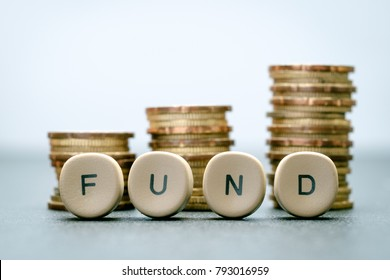 FUND letter blocks and stack coins, business concept.
