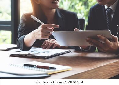 ファンドマネージャーは、デジタルタブレットで投資の分析株式市場に関する協議を行い、議論を行う。