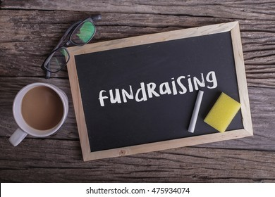 Fundraising On blackboard with cup of coffee, with glasses on wooden background