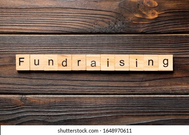 fundraising word written on wood block. fundraising text on table, concept.