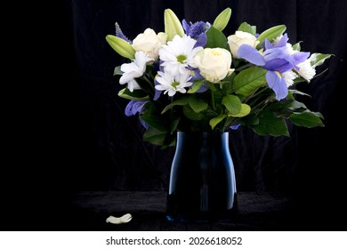 Funeral Bouquet purple White flowers, Sympathy and Condolence Concept on blackbackground with copy space.