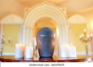 funeral, cremation and mourning concept - funerary urn and candles on table burning in church