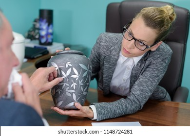 funeral director looking at urn with tearful client