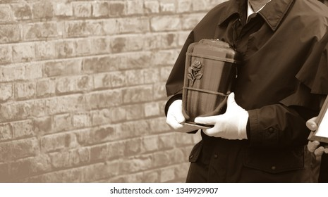 Funeral director or undertaker carrying a smooth metal urn in his hands, filled with ash towards the grave. Brick wall in the background. Funeral procession