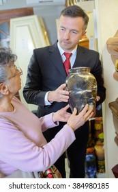 Funeral director with widow choosing urn