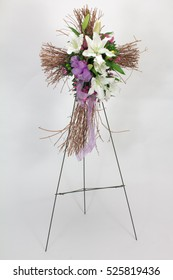 Funeral flower arrangement with cross made from twigs. Lilly in purple and white.