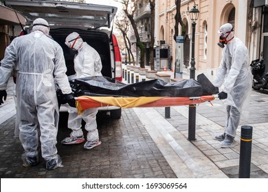 Funeral Home employees wear protective suits to protect themselves from Coronavirus, as they carry a dead body inside Bag.