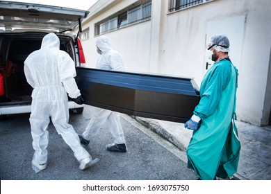 Funeral Home employees wear protective suits to protect themselves from Coronavirus, as they carry a coffin.
