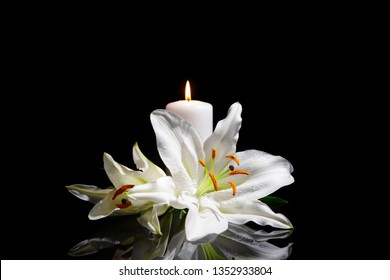 Funeral lily flowers and burning candle on dark background