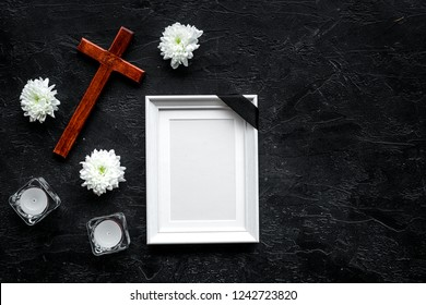 Funeral. Mockup of portrait of the deceased, of dead person. Frame with black ribbon near flowers, candles and cross on black background top view copy space