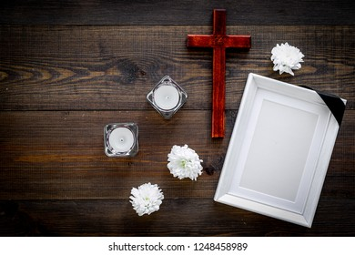 Funeral. Mockup of portrait of the deceased, of dead person. Frame with black ribbon near flowers, candles and cross on dark wooden background top view copy space