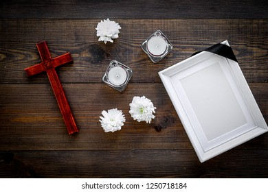 Funeral. Mockup of portrait of the deceased, of dead person. Frame with black ribbon near flowers, candles and cross on dark wooden background top view