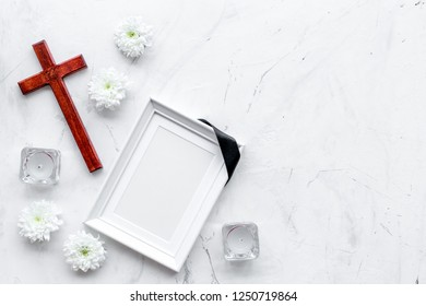 Funeral. Mockup of portrait of the deceased, of dead person. Frame with black ribbon near flowers, candles and cross on white background top view copy space