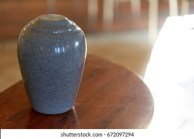 funeral and mourning concept - cremation urn on table in church