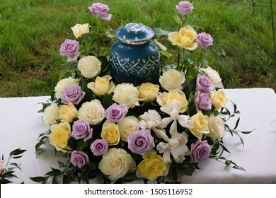 funeral and mourning concept - flowers surrounding urn
