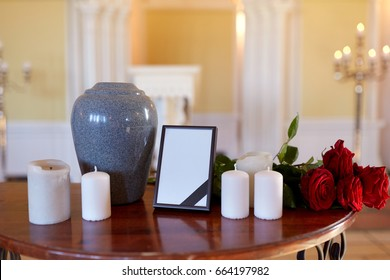 funeral and mourning concept - photo frame with black ribbon, cremation urn, flowers and candles on table in church