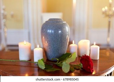 funeral and mourning concept - red rose and cremation urn with burning candles on table in church