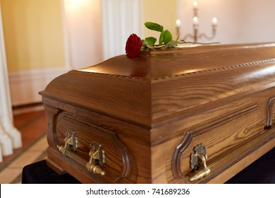 funeral and mourning concept - red rose flower on wooden coffin in church