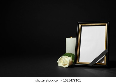 Funeral photo frame with ribbon, white rose and candle on dark table against black background. Space for design