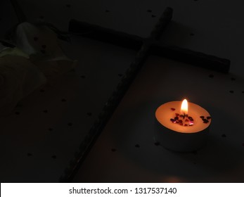 Funeral or rememberance. Candlelight flame in dark, christian christianity cross. Beautiful white roses and small red hearts in wax. Love, light on grey background. Spirituality. Part of a serie.